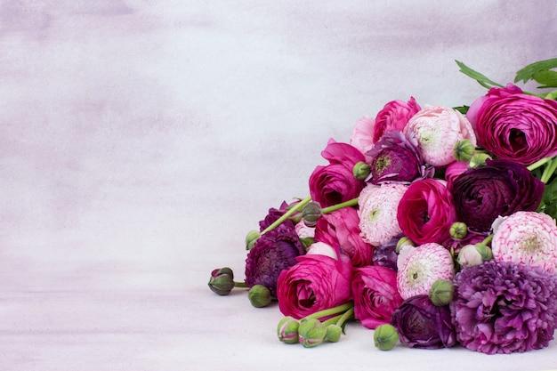 Su uno sfondo rosa un bouquet di ranuncoli