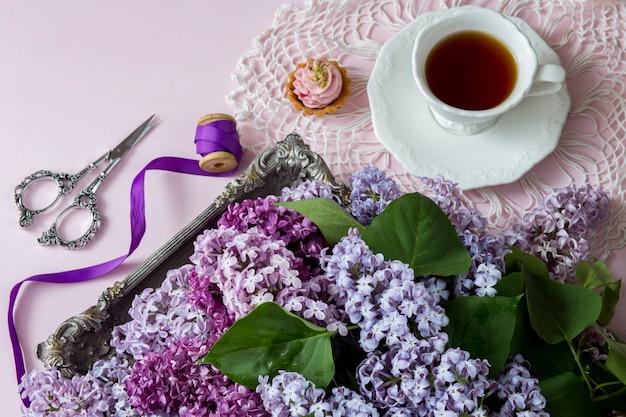 Su uno sfondo rosa un mazzo di fiori lilla in un vecchio piatto d'argento