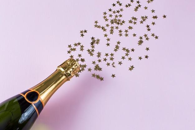 Su uno sfondo rosa una bottiglia di champagne e stelle dorate, come se schizzassero.