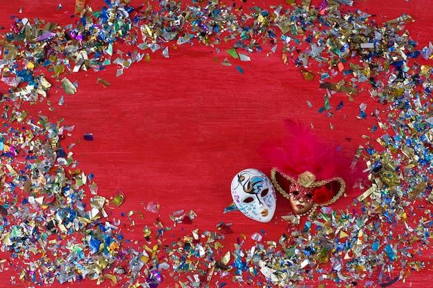 Su uno sfondo rosso ci sono due maschere di carnevale e coriandoli colorati intorno