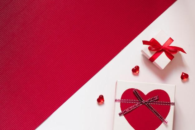 Su uno sfondo rosso e bianco, scatole regalo e un fiocco rosso, cuori di vetro rosso cuori