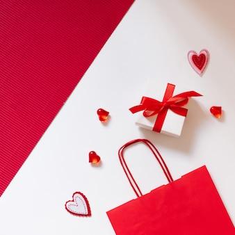 Su uno sfondo rosso e bianco, una confezione regalo con un fiocco rosso, una shopping bag di carta rossa, cuori di cuori di vetro rosso.