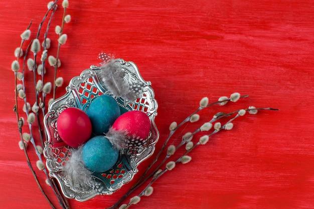 Su uno sfondo rosso un piatto con uova dipinte e salice - sfondo di pasqua