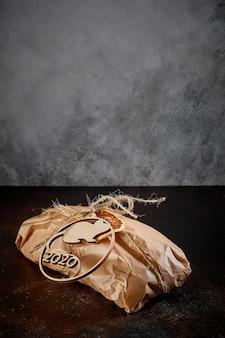 Su uno sfondo scuro di trama un pacco regalo in carta kraft legato con spago con l'emblema del topo simbolo del nuovo anno in compensato