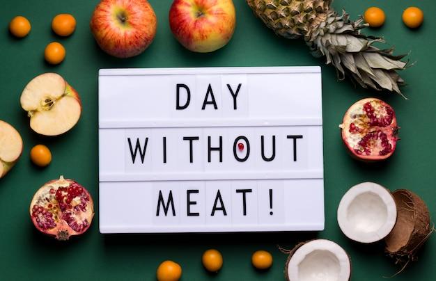 Su uno sfondo verde c'è una lightbox con il frutto del testo adiacente. concetto di giornata internazionale senza carne