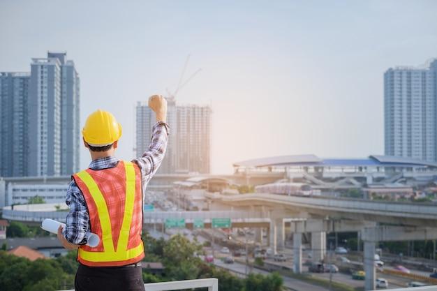 Successo dell'ingegnere che lavora e tenere la mano in alto