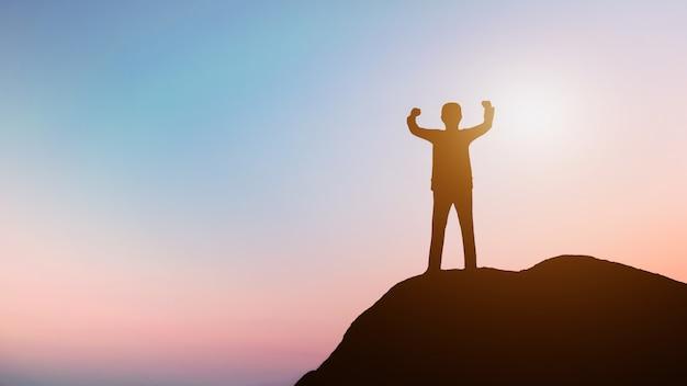 Successo o vincitore dell'uomo d'affari sul picco superiore della montagna delle rocce al tramonto, concetto del capo