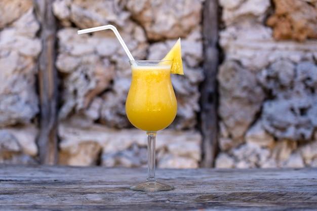 Succo appena spremuto di ananas in un calice di vetro sullo sfondo di un vecchio muro di pietra