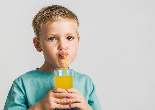 Succo bevente del bambino sveglio del primo piano