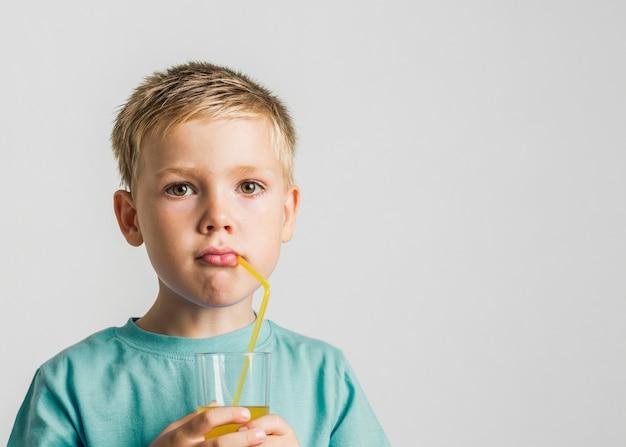Succo bevente del ragazzo dei capelli biondi di vista frontale