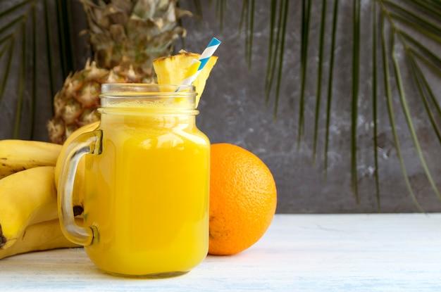 Succo d'ananas in un barattolo con una cannuccia.