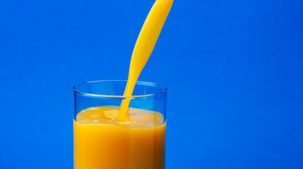Succo d'arancia che versa nel vetro, isolato su fondo blu