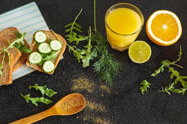 Succo d'arancia con una fetta d'arancia e sandwich di verdure su sfondo nero