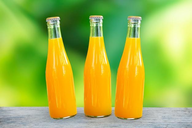 Succo d'arancia confezionato in bottiglie di vetro piano in legno e sfondo verde della natura