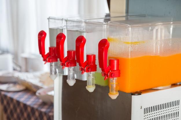 Succo d'arancia e acqua nel distributore e bicchieri sul tavolo per la festa