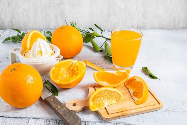 Succo d'arancia e arance fresche spremute frutta sul tavolo di legno bianco. fatti in casa