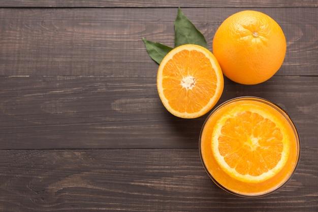 Succo d'arancia e arance freschi su fondo di legno