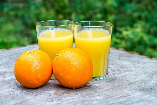 Succo d'arancia fresco con la frutta delle arance all'aperto