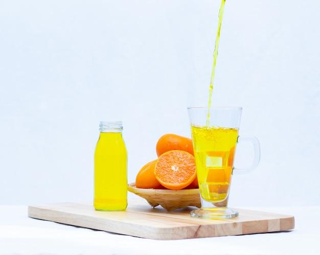 Succo d'arancia giallo nei bicchieri e bottiglia su sfondo bianco,