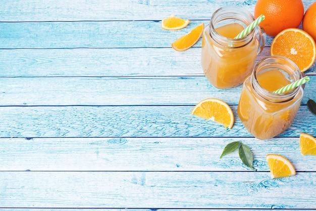 Succo d'arancia in barattoli di vetro e arance fresche su sfondo blu.