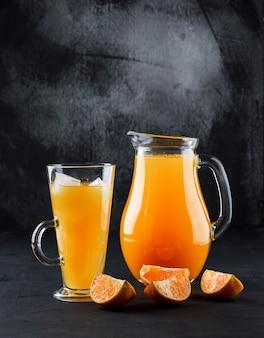 Succo d'arancia in tazza di vetro e brocca con fette d'arancia