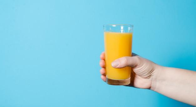 Succo d'arancia in un bicchiere in una mano. il concetto di una vita sana