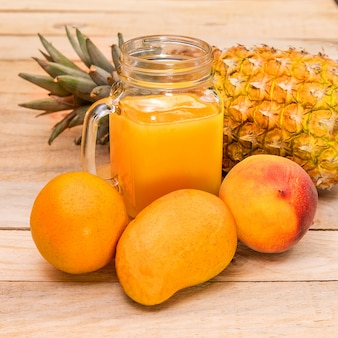 Succo d'arancia, mango e ananas su un tavolo di legno