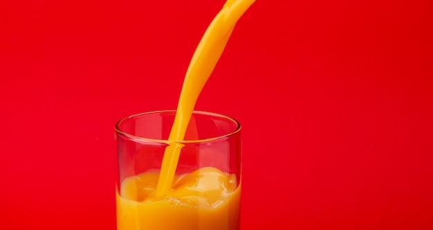 Succo d'arancia versando nel bicchiere, isolato su sfondo rosso