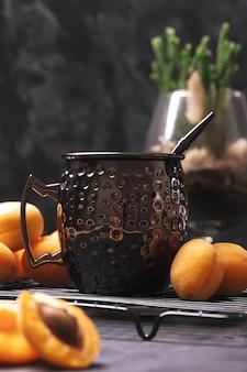 Succo di albicocca e frutta fresca. le albicocche si trovano su sfondo scuro. colpo basso chiave