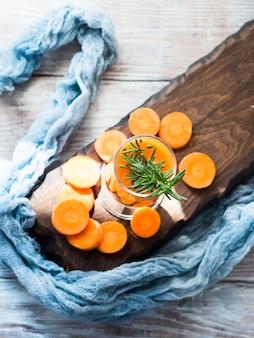 Succo di carota arancia sul bordo di legno