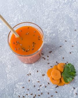 Succo di carota detox nutriente in vetro con semi di lino e foglie di prezzemolo. concetto di dieta alcalina. bevanda vegetariana biologica
