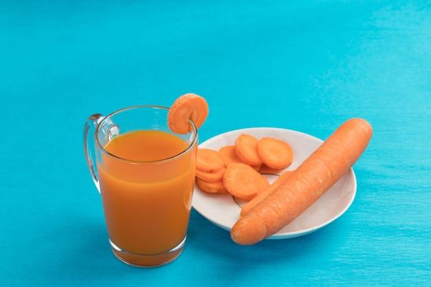 Succo di carota in un bicchiere sul blu