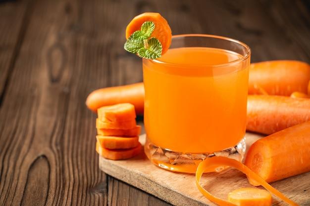 Succo di carota in vetro sulla tavola di legno.