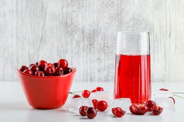 Succo di ciliegia con ciliegie, cubetti di ghiaccio in un bicchiere su bianco