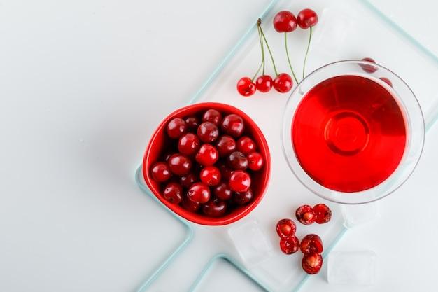 Succo di ciliegia con ciliegie in un bicchiere su bianco e tagliere