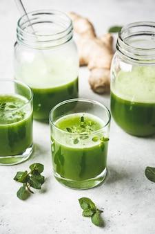 Succo di disintossicazione verde con zenzero e menta in bicchieri e vasetti