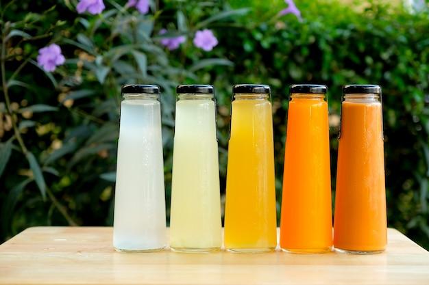 Succo di frutta organico freddo in bottiglia di vetro sulla tavola di legno al giardino.