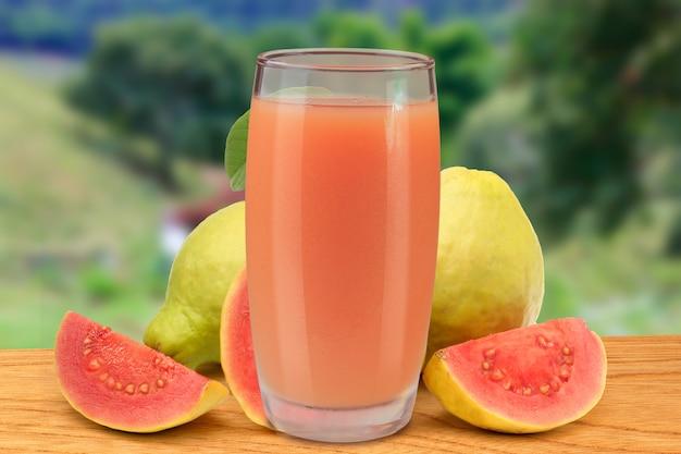 Succo di guava fresco in tazza di vetro sulla tavola di legno della natura e dell'azienda agricola