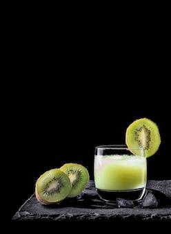 Succo di kiwi con ghiaccio su sfondo nero e due pezzi di kiwi