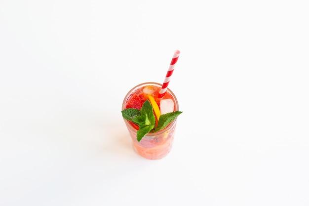 Succo di limonata alla fragola fredda con cubetti di ghiaccio, menta, limone, tubo per cocktail e su sfondo bianco. bevanda estiva fredda.