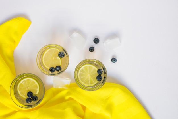 Succo di limone con mirtilli e cubetti di ghiaccio su sfondo bianco