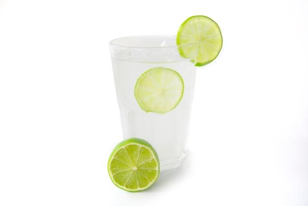 Succo di limone fresco in un vetro trasparente decorato con la fetta di vista laterale del limone isolato su fondo bianco