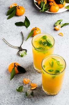 Succo di mandarino in bicchieri sulla luce