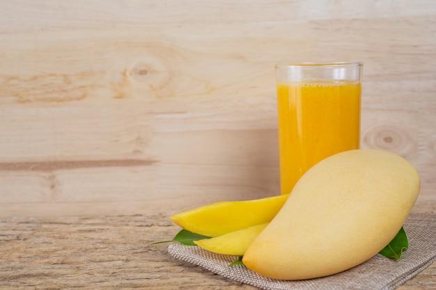 Succo di mango sul tavolo del pavimento in legno.