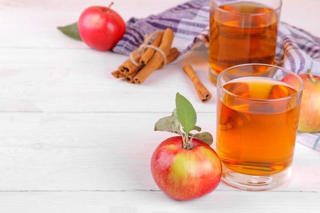 Succo di mela con belle mele fresche e cannella su un fondo di legno bianco