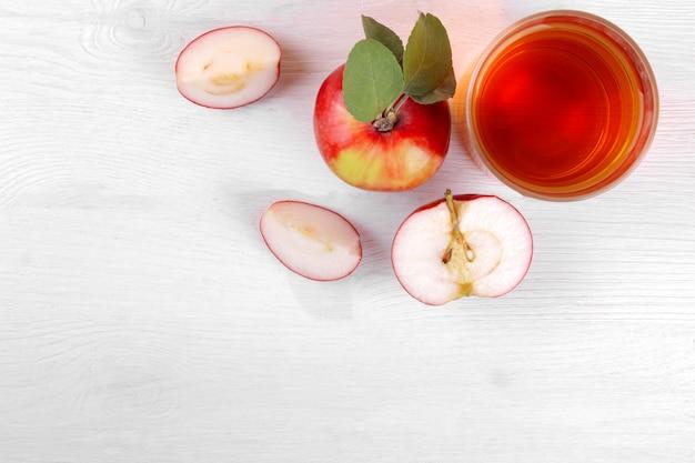 Succo di mela con mele fresche belle su un fondo di legno bianco.