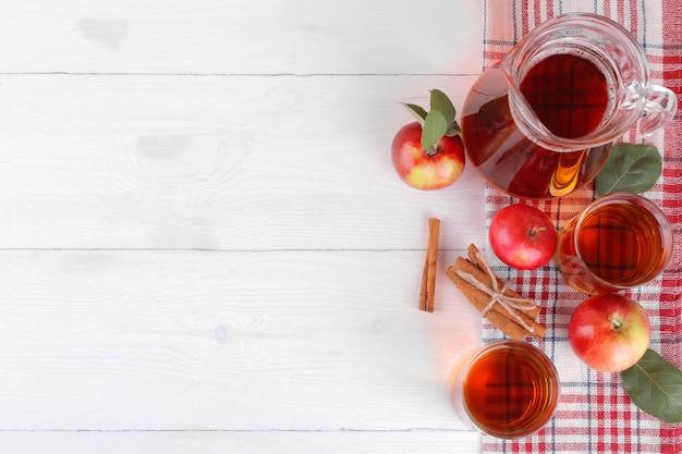Succo di mela con mele fresche e cannella su un fondo di legno bianco