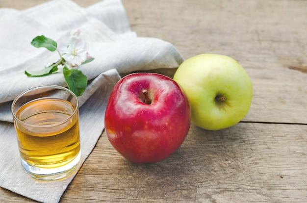 Succo di mela e mele su un tavolo di legno con una tovaglia grigia