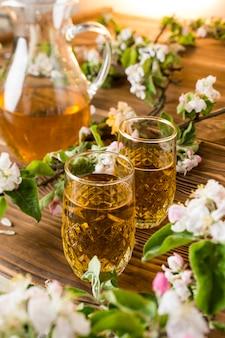 Succo di mela in un bicchiere con fiori di mela sul tavolo