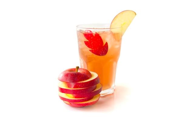 Succo di mela in un vetro trasparente decorato con una fetta di mela rossa vista laterale isolato su sfondo bianco